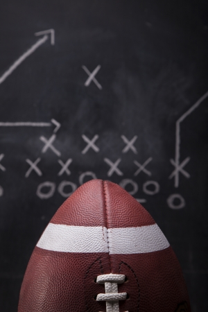An American football with a play drawn up on a chalkboard in the background