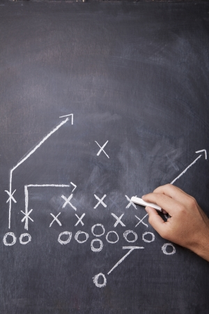 A hand draws a football play on a chalkboard with chalk leaving room for copy