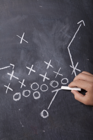 A hand draws a football play on a chalkboard with chalk