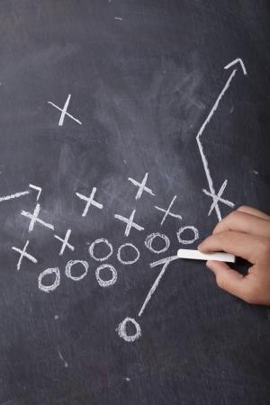 football play: Una mano disegna un gioco di calcio su una lavagna con il gesso