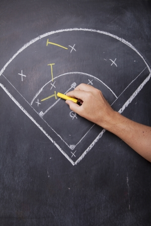 baseball diamond: A man draws the positioning of a baseball team on a chalkboard  Stock Photo