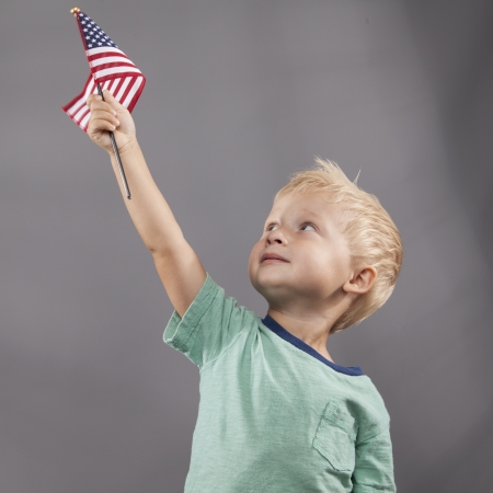 A young boy looks up at an American flag that he holds proudly above his head.