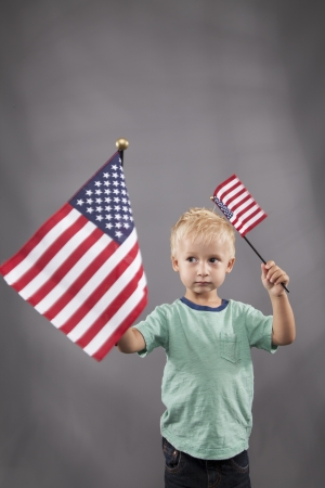 A young boy stands and waves two flags in his hands.