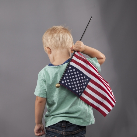 A young boy holds an American flag proudly over his shoulder. photo