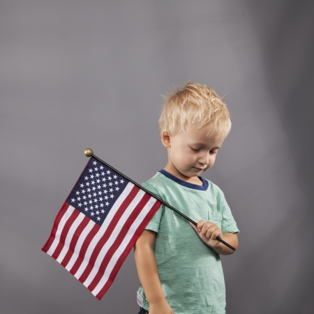 pledge: A young boy holds an American flag over his shoulder. Stock Photo