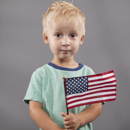 I young boy holds tightly on to the American flag. Stock Photo - 15070121