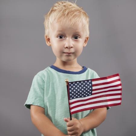 salut: Jag ung pojke håller hårt på den amerikanska flaggan.