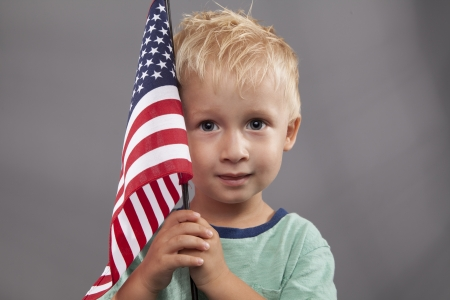 salute: A cute young boy holds an American flag next to his head.