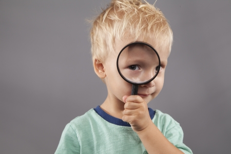A cute young boy holds a magnifying glass up to his eye. photo