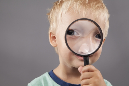 detect: A young boy smiles and holds a magnifying glass up to his face.  Stock Photo