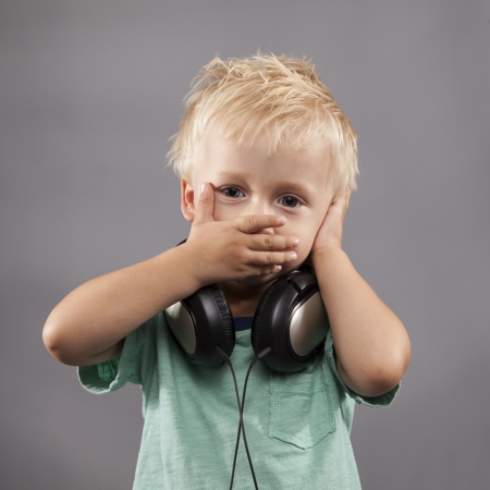 hands over ears: A LIttle Boy with headphones holds hands over ears and mouth.
