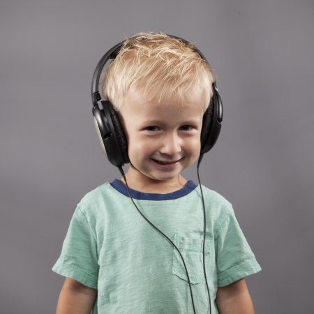 A young boy smiles with headphones on his head. Stock Photo
