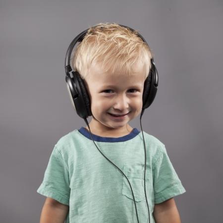 Un giovane ragazzo sorride con le cuffie in testa. Archivio Fotografico - 15070120