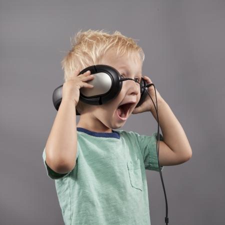 niño cantando: Muchacho joven sostiene los auriculares en sus oídos mientras él canta.