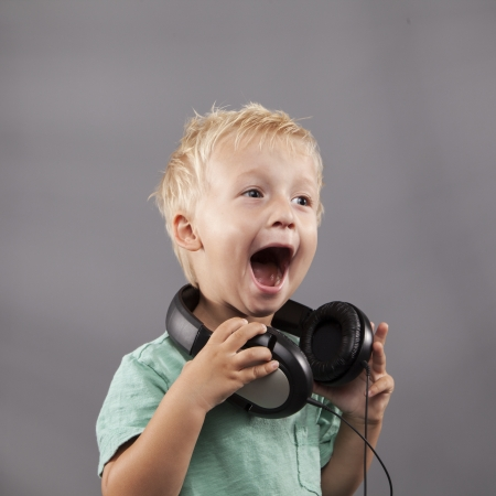 A happy young boy with headphones around his neck sings loudly. Stock fotó