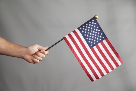 extends: An arm extends and holds a big American Flag  Stock Photo