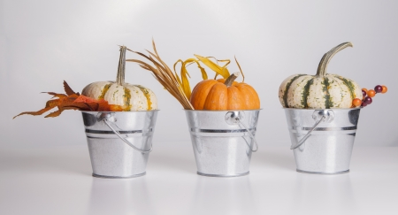 Three metal buckets are filled with fall pumpkins and decorations  photo