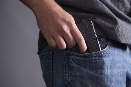 man holding gun: A man legally carries a firearm in his pocket for protection