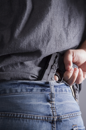 man holding gun: A man conceals a firearm in the back of his pants