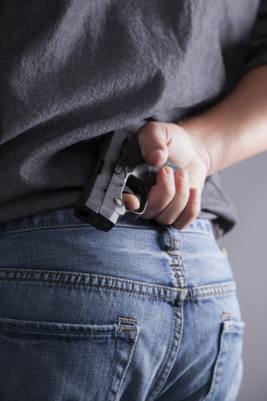 concealed: A man conceals and holds a loaded gun behind his back