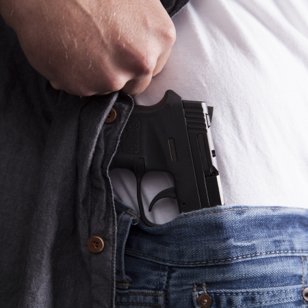 man holding gun: A man reveals a concealed firearm at his side