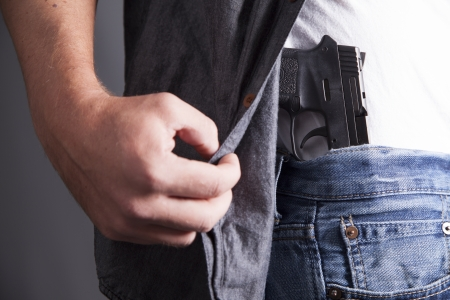 man holding gun: A man reveals a concealed pistol at his side
