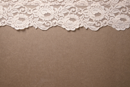 beige: Light pink lace trim sits on a wooden background