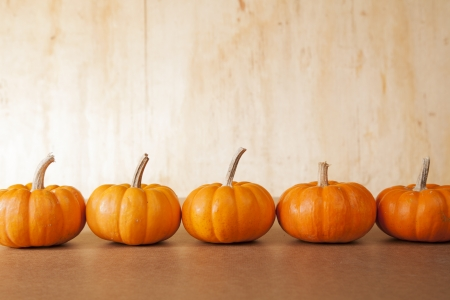 Five orange pumpkins sit in a row in front of a distressed, wooden background