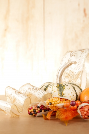thanksgiving background: A group of gold and orange fall items sit against a wooden backround