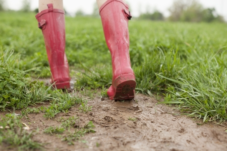A pair of pink rain boots walk through a muddy patch of grass