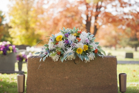 A colorful spray of flowers grace the top of a tombstone in the fall