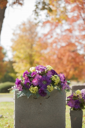 A beautiful spray of purple flowers grace the top of a tombstone in the fall
