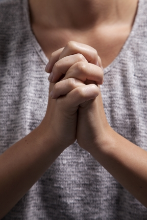 A yound woman clasps her hands in prayer