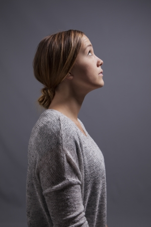 A young woman looks upward and ponders