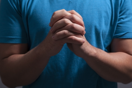 baptist: A man clasps his hands and prays alone