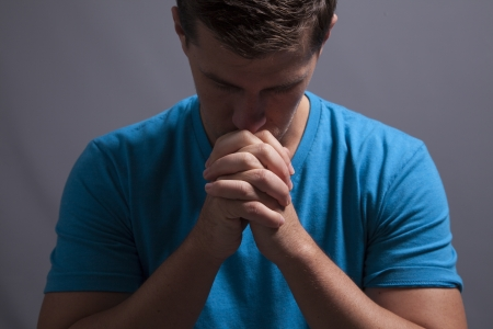 clasps: A man clasps his hands and prays alone
