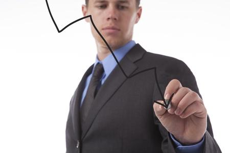Young business man draws a declining arrow representing loss.  Stock fotó