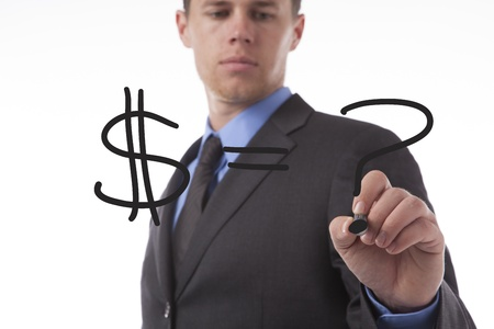 Young business man draws a dollar sign and a question mark.  photo