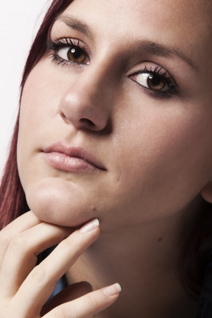 A beautiful young redhead woman is in deep thought.