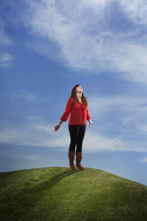 A composite of a young girl standing atop a grass hill enjoying the day.  Stock fotó