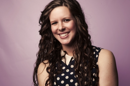 A beautiful young woman wearing polka dots smiles on an isolated background.