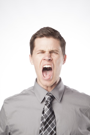 loudly: A young business professional screams loudly in frustration