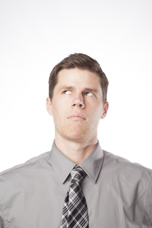 A young business professional looks up and thinks while expressing confusion