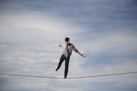 balance concept: Young businessman balancing on a rope in the sky.