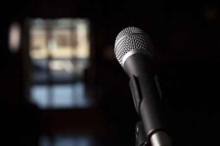 A close up of a microphone with coloful bocca in background