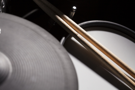 drum and bass: A close up shot of drumsticks on a set of electric drums  Stock Photo