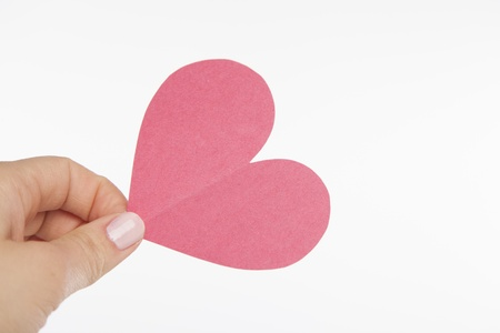 A hand holds on to a pink heart cut out of construction paper  Stock fotó