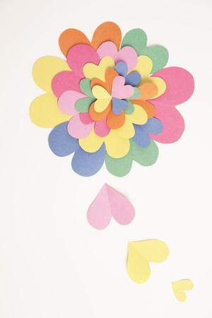 Many cut out paper hearts form together to make a big colorful flower