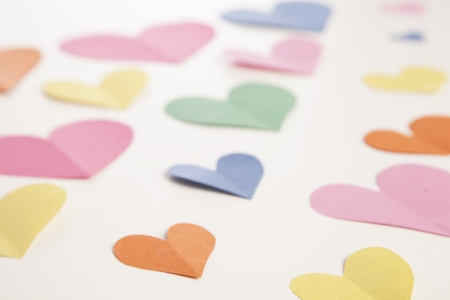 Colorful paper hearts are cut out of construction paper to form a background