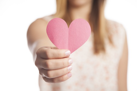 A young woman holds out a cut out construction paper heart  Imagens